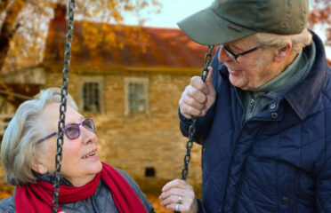 Older couple connecting on swing set